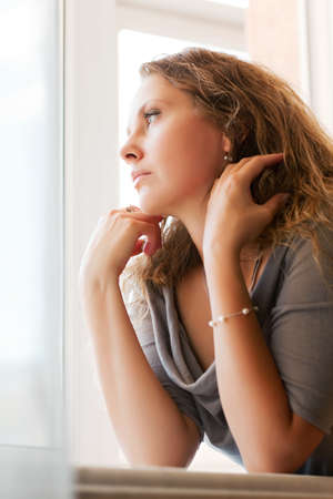 Sad woman looking out the window photo