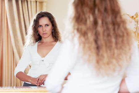Beautiful woman looking in the  mirror photo