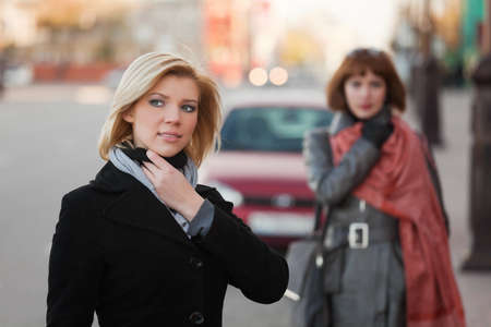 Two young women walking on the city street photo