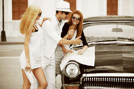 urban road: Young tourists with a road map on the retro car Stock Photo