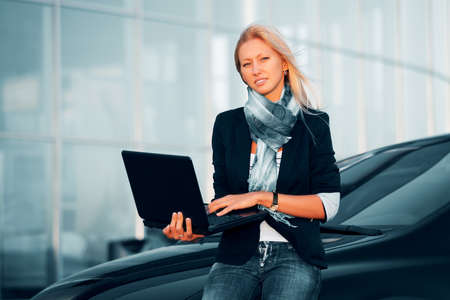 Young businesswoman with laptop on the parking photo