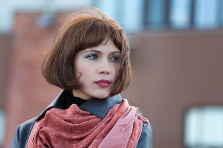 red scarf: Sad beautiful  woman on the city street Stock Photo