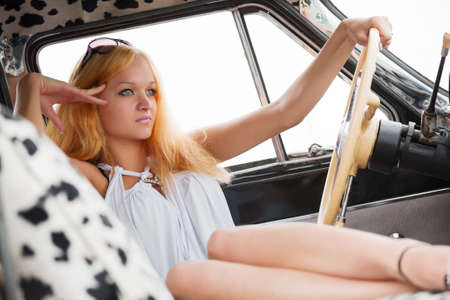 Young blond woman relaxing in a retro car photo