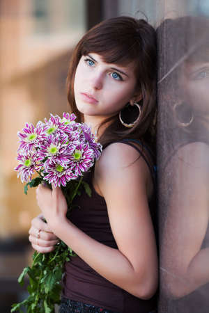 Sad young woman with bouquet of chrysanthemums photo