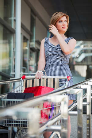 Young woman with shopping cart photo
