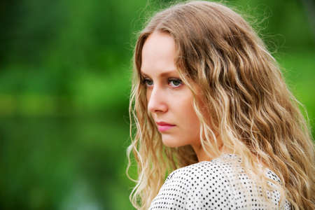 Sad young woman against a nature background photo