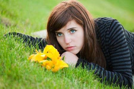 mujer pensativa: Triste joven tumbado en la hierba