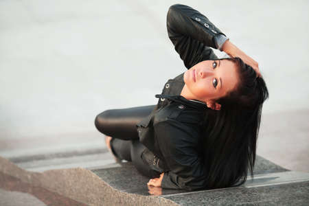 Young woman relaxing on the city sidewalk photo