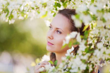 Beautiful woman among blossoming trees photo