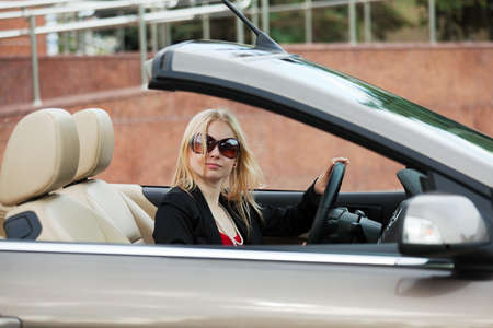 Young woman driving a convertible  photo