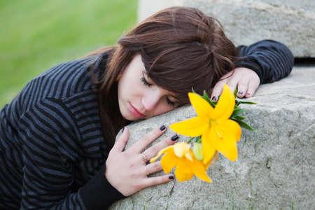 tumbas: Joven tumbado en la l�pida Foto de archivo