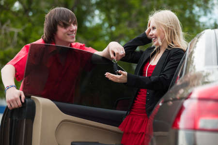 Young man is giving car key to his girlfriend photo