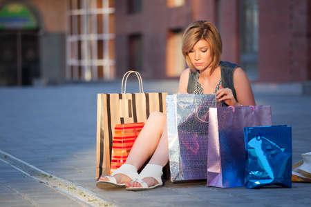 wśród: MÅ'oda kobieta siedzi poÅ›ród toreb na zakupy