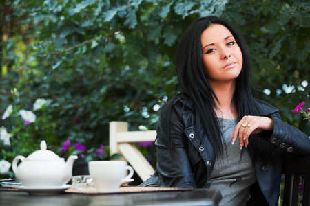 Young woman drinking tea at sidewalk cafe photo
