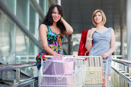 carro supermercado: Dos mujeres j�venes con carro de compras