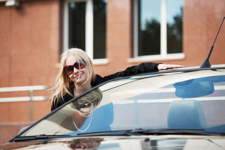 Happy young woman with a new convertible car photo