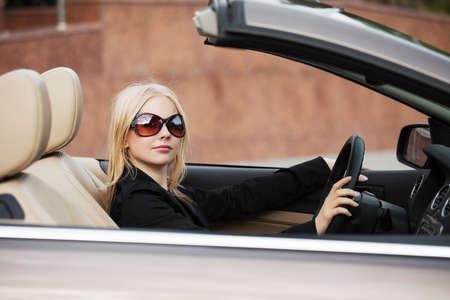 Young woman driving a convertible car photo