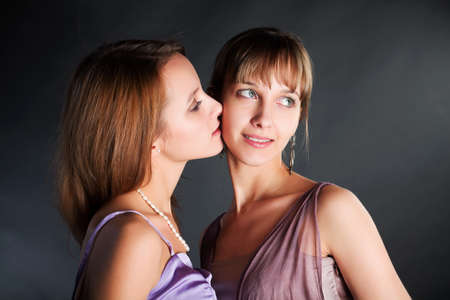Two young beautiful women on the dark background photo
