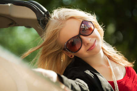 Happy young blond with a new convertible car photo