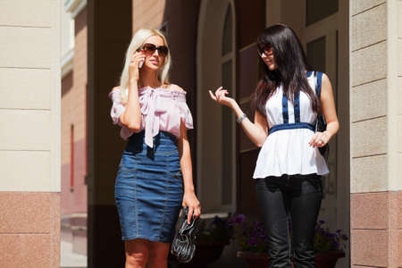 Two young women walking on a city street photo