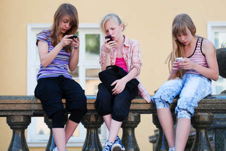 Teenage girls calling on the mobile phones Stock Photo