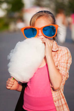 Girl eating cotton candy photo