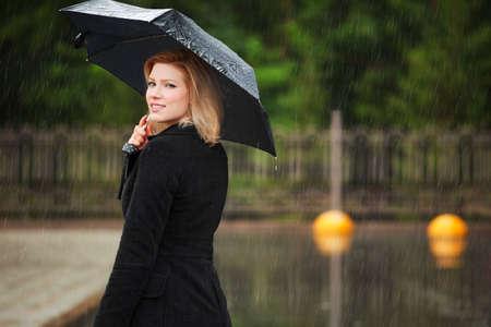 Mujer con paraguas en la lluvia Foto de archivo