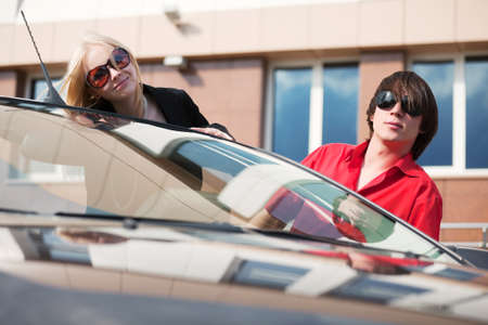 Happy young couple with a new convertible car photo