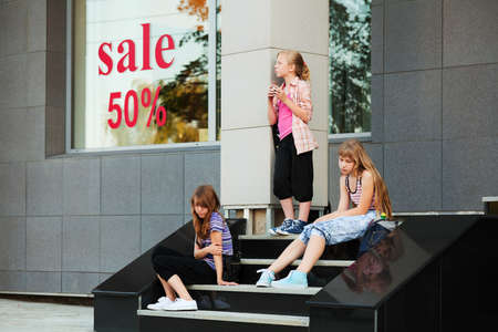 Teenage girls relaxing on a shop steps photo