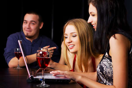 Young friends working on laptop in a bar Stock Photo - 10649825