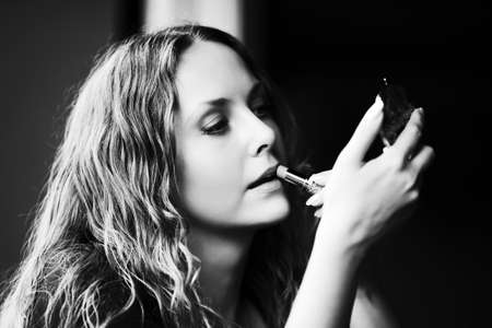 Beautiful woman applying a lipstick photo