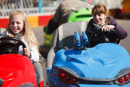 Teenage girls driving a bumper cars photo