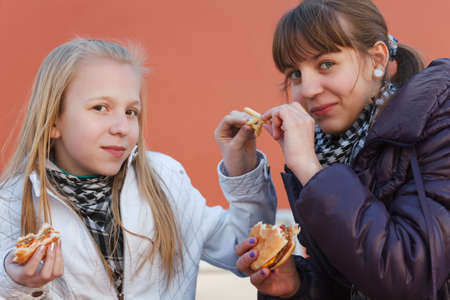 Teenage girls eating a burgers photo