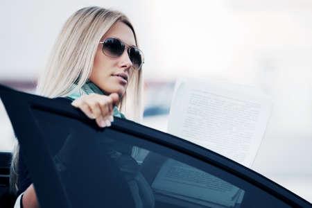Junge Unternehmerin mit einem Auto