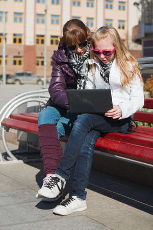 Teenage schoolgirls using laptop on the bench photo