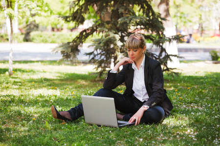 Businesswoman using laptop in a city park photo