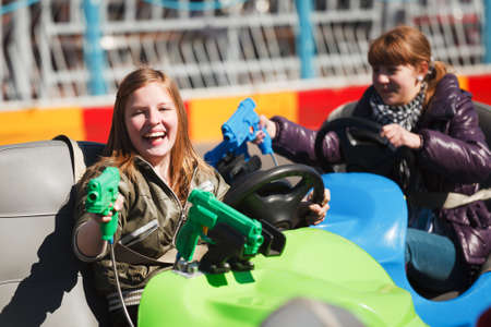 Teenage girls driving a bumper cars photo