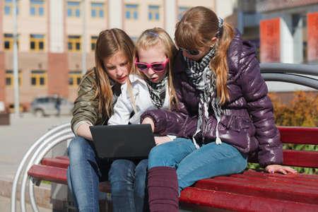 Schoolgirls using laptop  photo