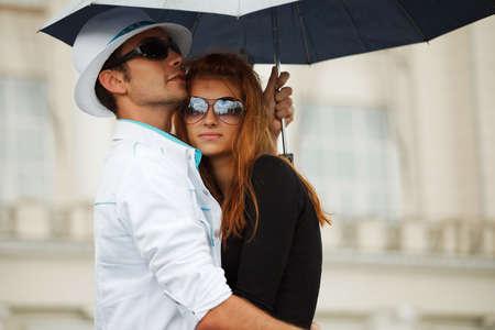 雨の中傘を持つ若いカップルします。