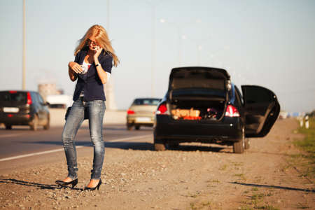 broken car: Young woman with a broken car calling for help