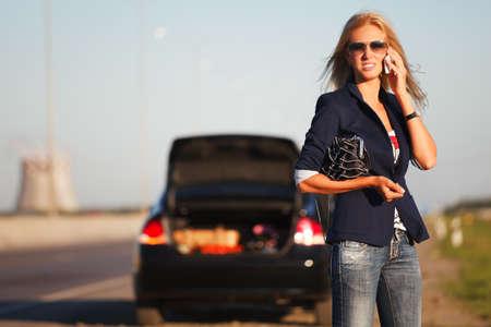 broken car: Mujer joven con una vocaci�n coche averiado en busca de ayuda Foto de archivo