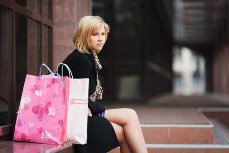 Mujer triste joven con bolsas de la compra