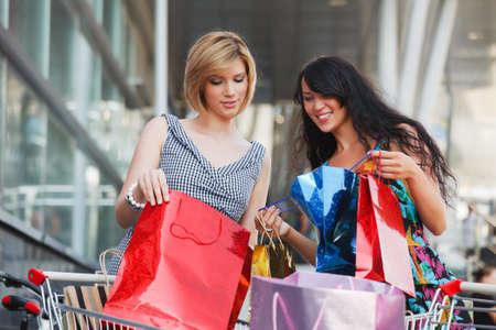 Las mujeres j�venes con carrito de la compra
