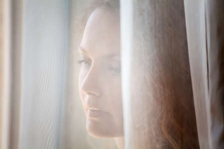 Sad Frau schaut durch das Fenster