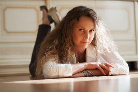 Beautiful woman lying on the parquet floor photo