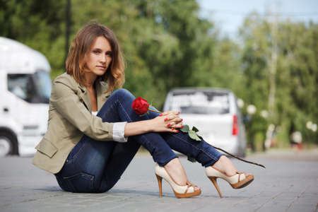 Sad young woman with a rose photo