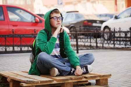 sad boy: Young man sitting against a city traffic