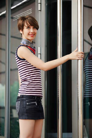Young woman against a shop door photo