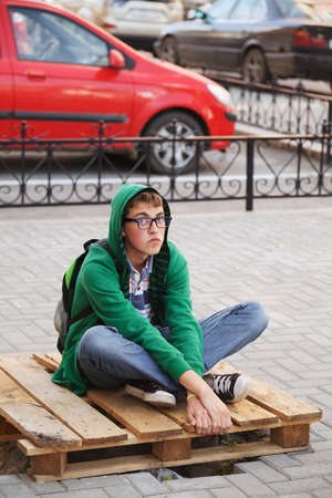 Young man sitting on a sidewalk photo