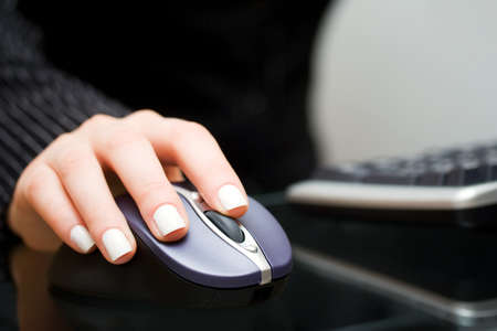 use computer: Female hand holding computer mouse Stock Photo